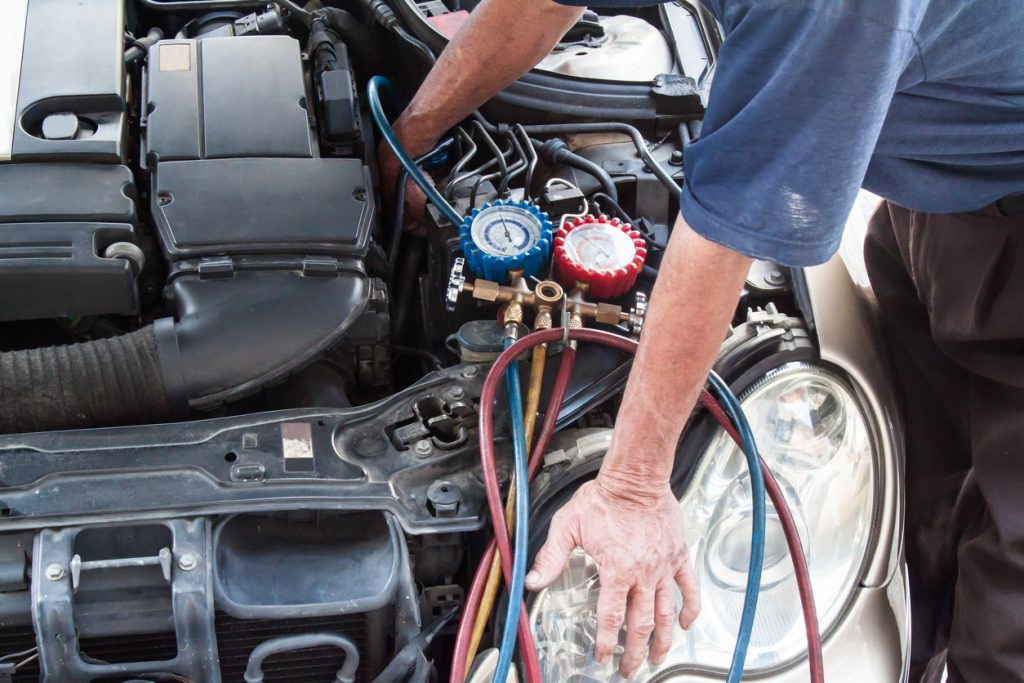 Mechanic with manometer inspecting vehicle heating system