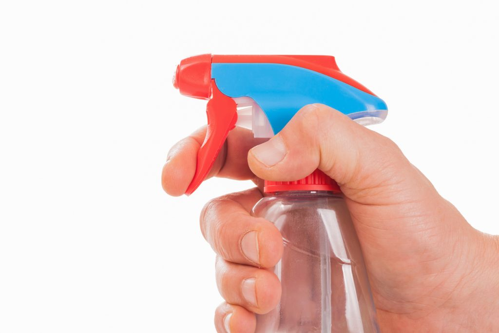 Hand with spray bottle ready for cleaning stains