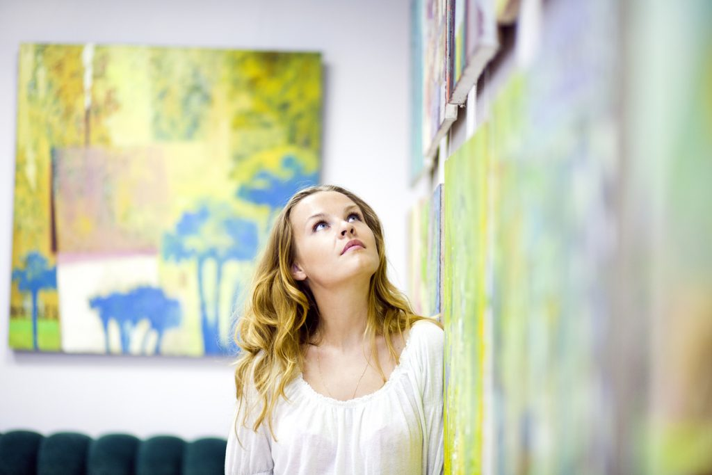 Artistic woman gazing at artwork on the wall