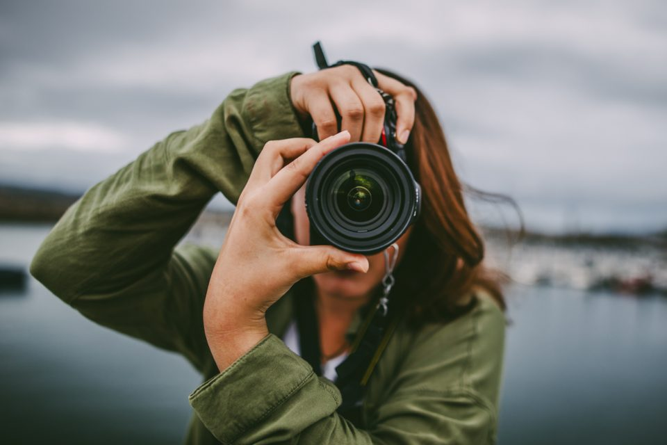 Young artistic woman using DSLR camera