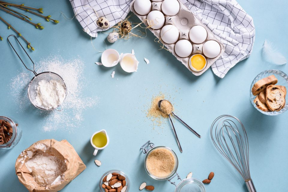 Dessert ingredients - flour, eggs, butter, sugar, yolk, almond nuts on blue table. Sweet pastry baking.