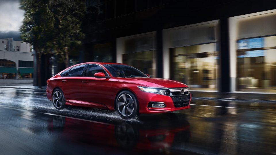 Red 2020 Honda Accord driving down a rainy street at night