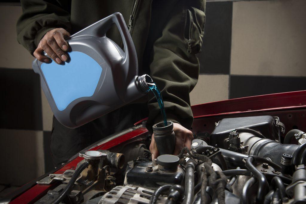 Auto repairman pouring antifreeze into radiator