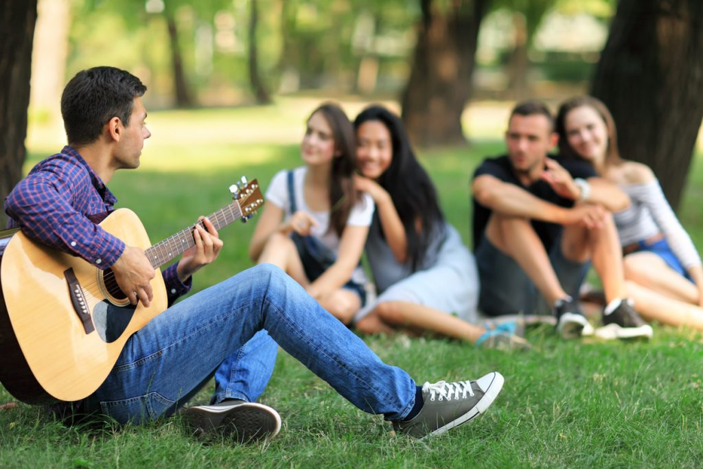 Man playing guitar at music events in the park