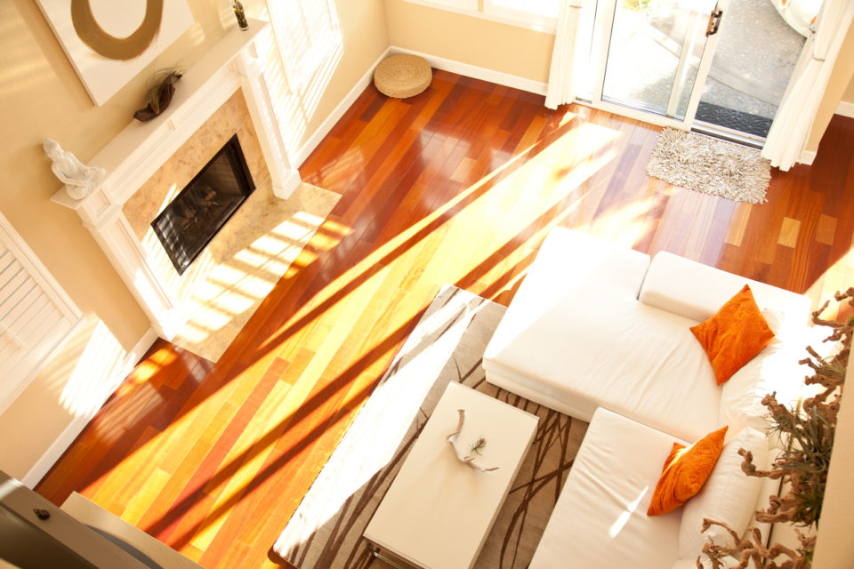 High angle view of an empty modern living room with a fireplace, hardwood floors, a white sofa and orange pillows.
