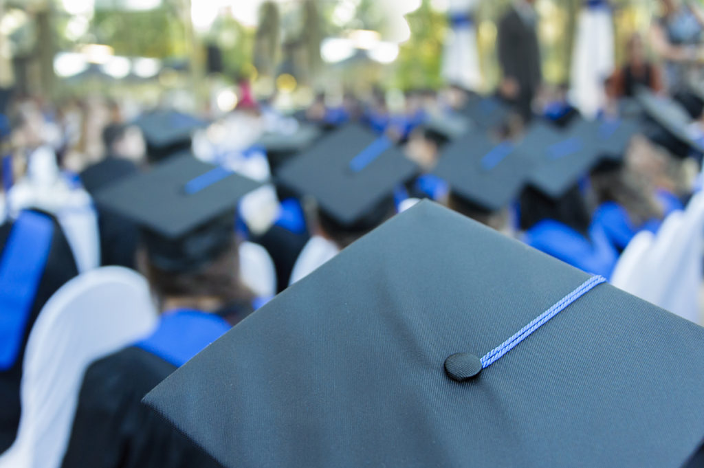 Closeup of mortarboard hats as students attend their graduation