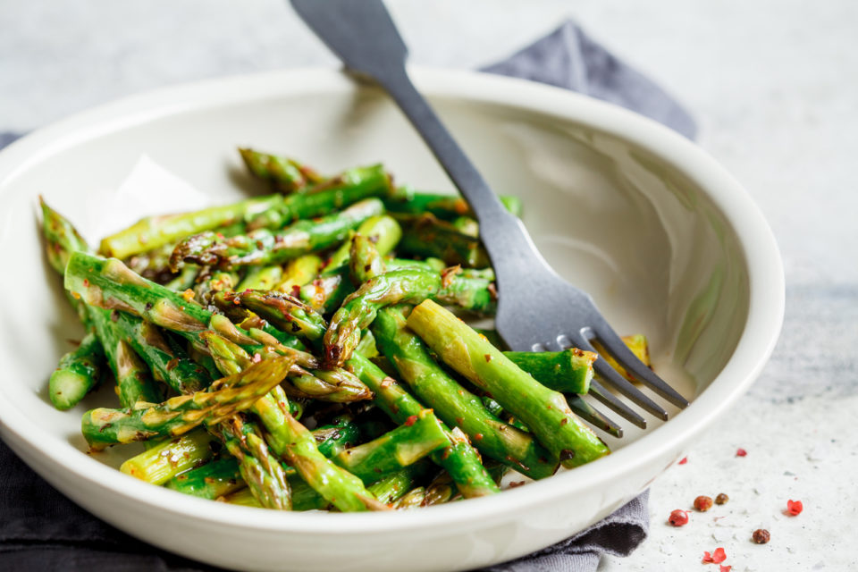 Green asparagus with pepper and salt in a white bowl.