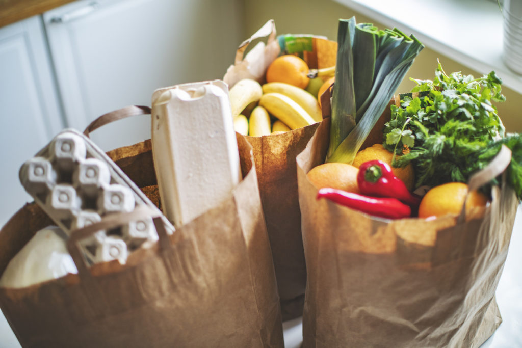 paper bags of groceries including eggs, fruit, leeks, and chiles