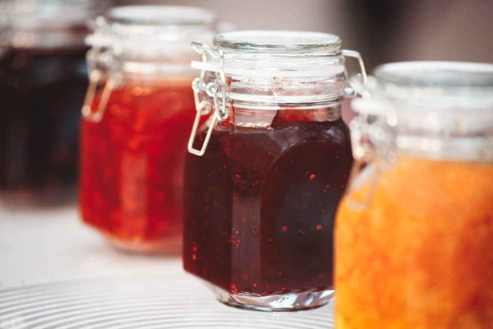 Glass jars with butter and jam on a wooden shelf